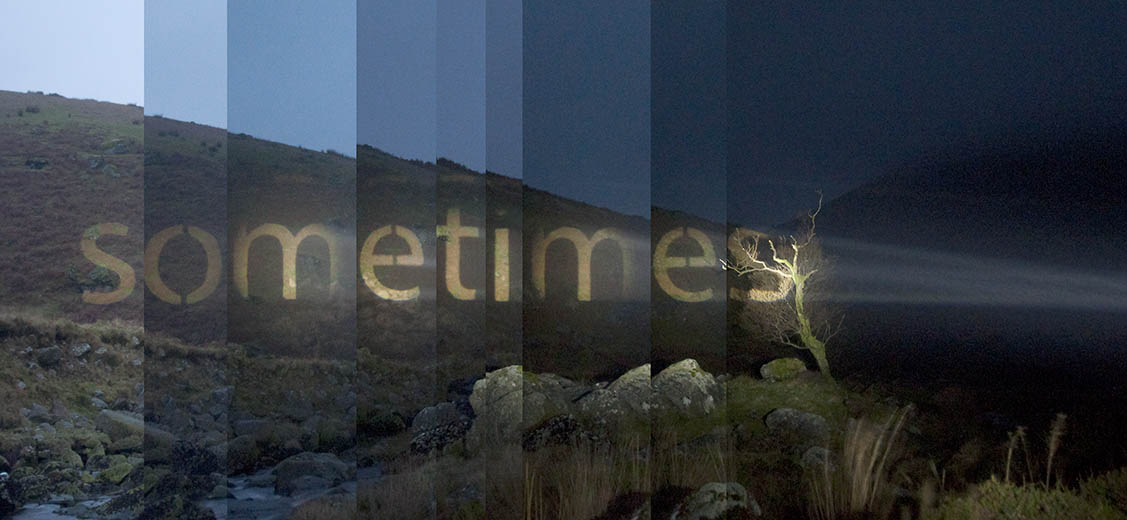 Link to a projector project by Michael Cross. Text works made with a powerful projector that projects words onto the landscape. Image shows the word Sometimes projected onto a hillside.