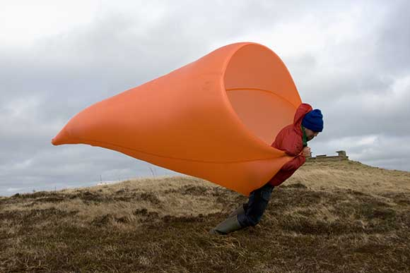 A man holds a large orange fabric funnel like a wind sock, it is filled by the wind and he's fighting to stand upright.